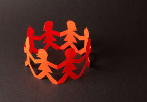 Group of paper doll holding hands. Teamwork concept papercraft. Orange dolls on black wooden background