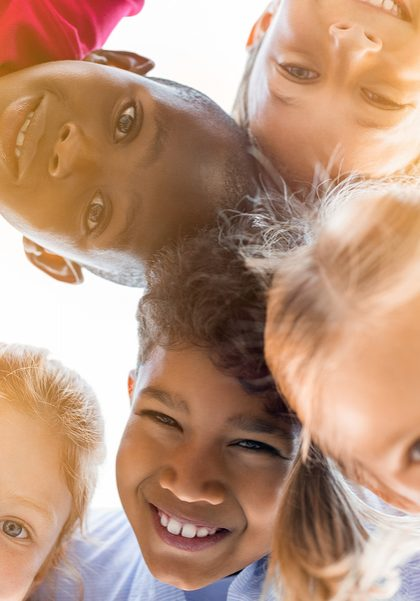 Portrait of happy kids in circle looking down and embracing. Group of five multiethnic friends outdoor looking at camera and smiling. Closeup face of children looking at camera together at park.